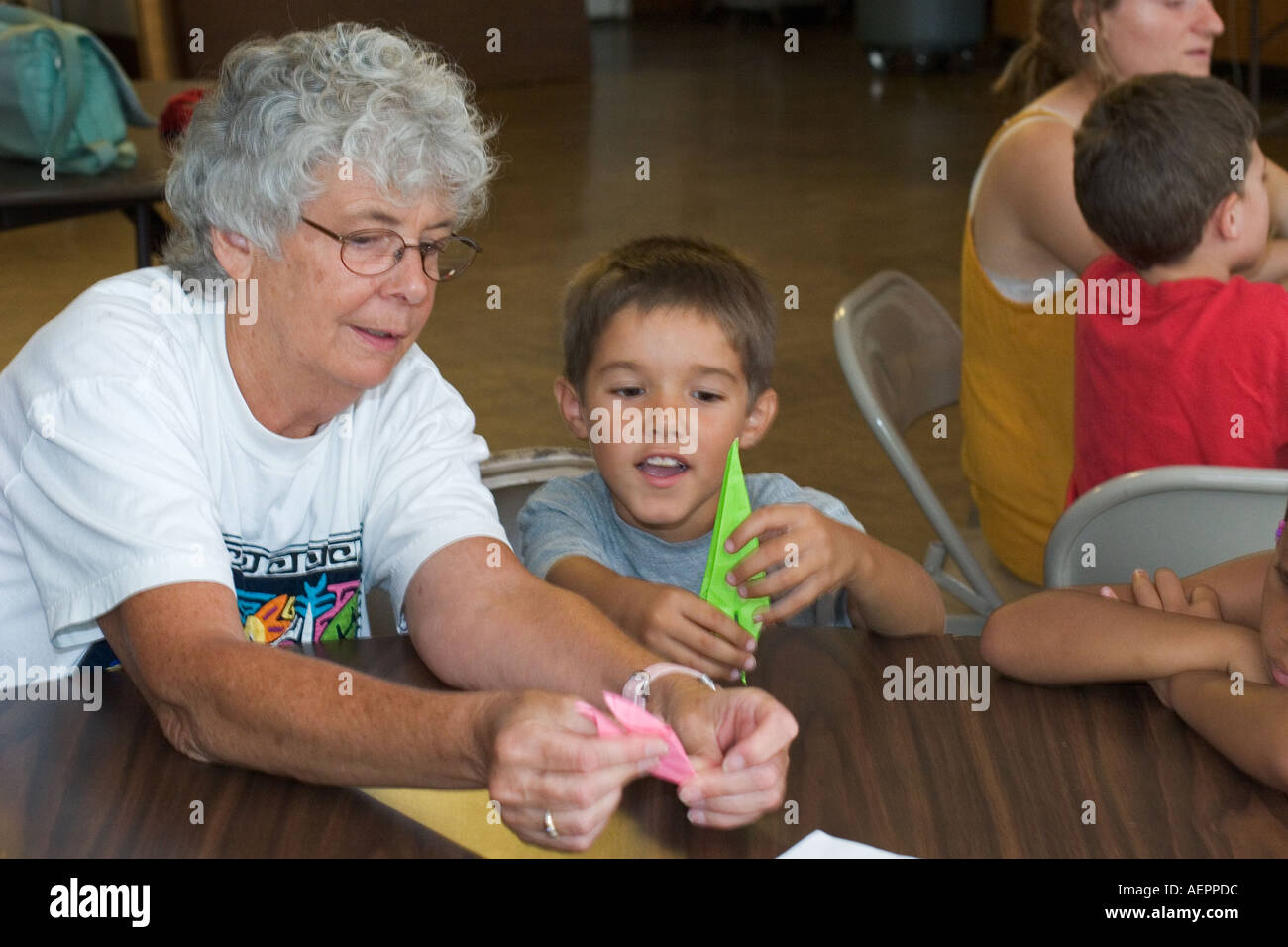 Child Learns to Fold Paper Cranes at Peace Camp - Stock Image