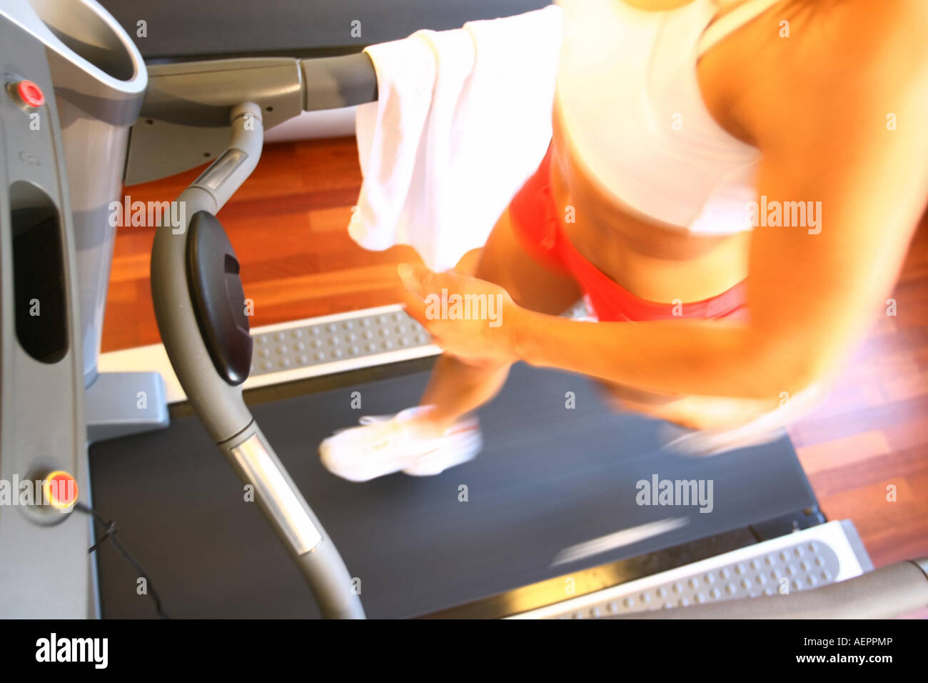 Young woman is training with a treadmill ,Junge Frau laeuft auf einem Laufband in einem Fitnessstudio - Stock Image