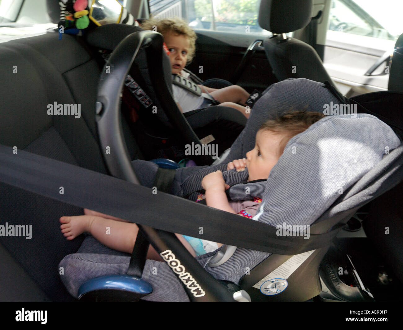 Children in Forward and Rear Facing Car Seats in Back of Car Stock