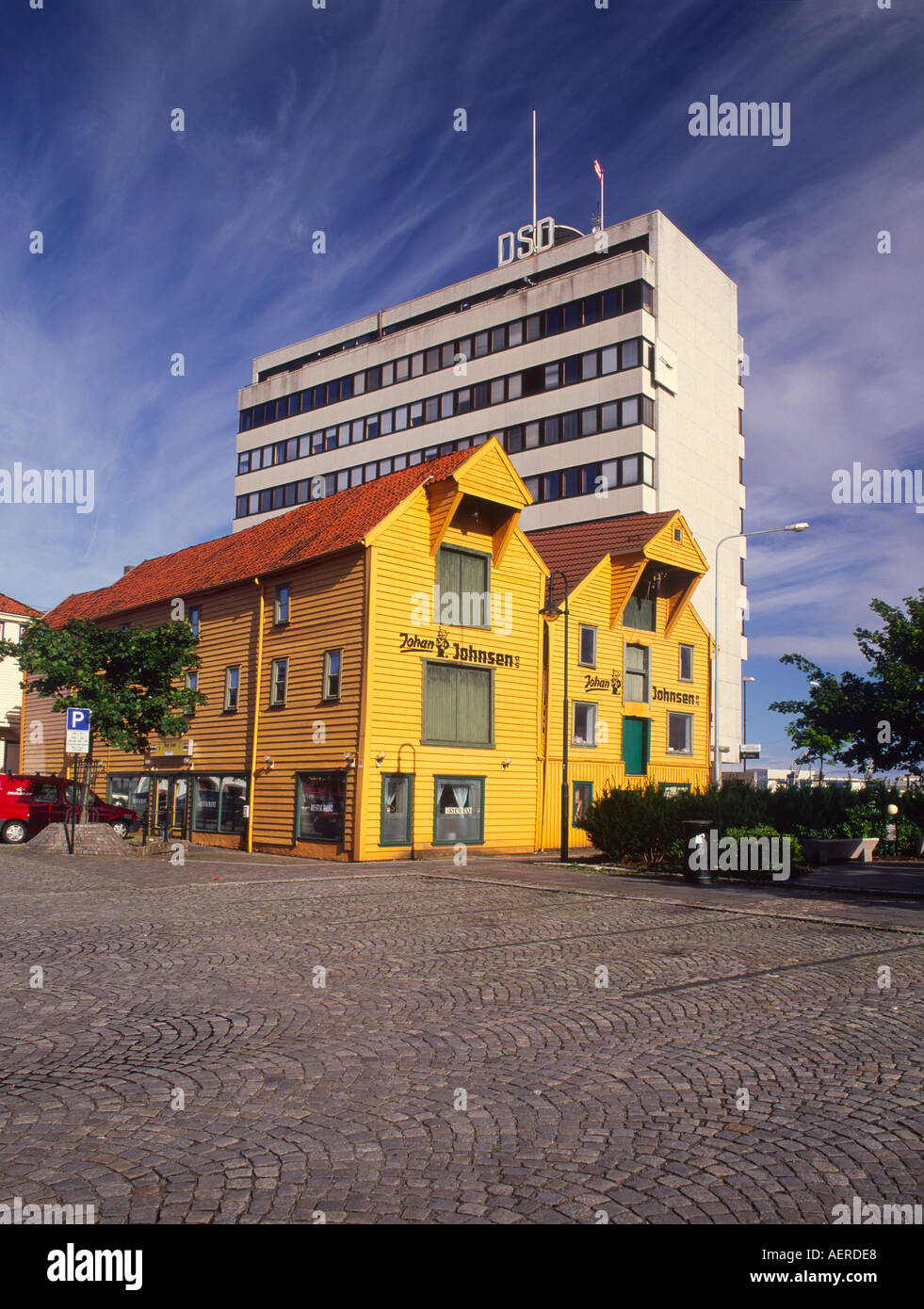 Typical Norwegian Seahouse sits adjacent to a modern concrete tower building - Stock Image
