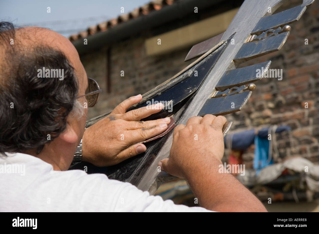 Craftsman using sandpaper to prepare gondola for repainting in the boatyard of D Tramontin Figli - Stock Image