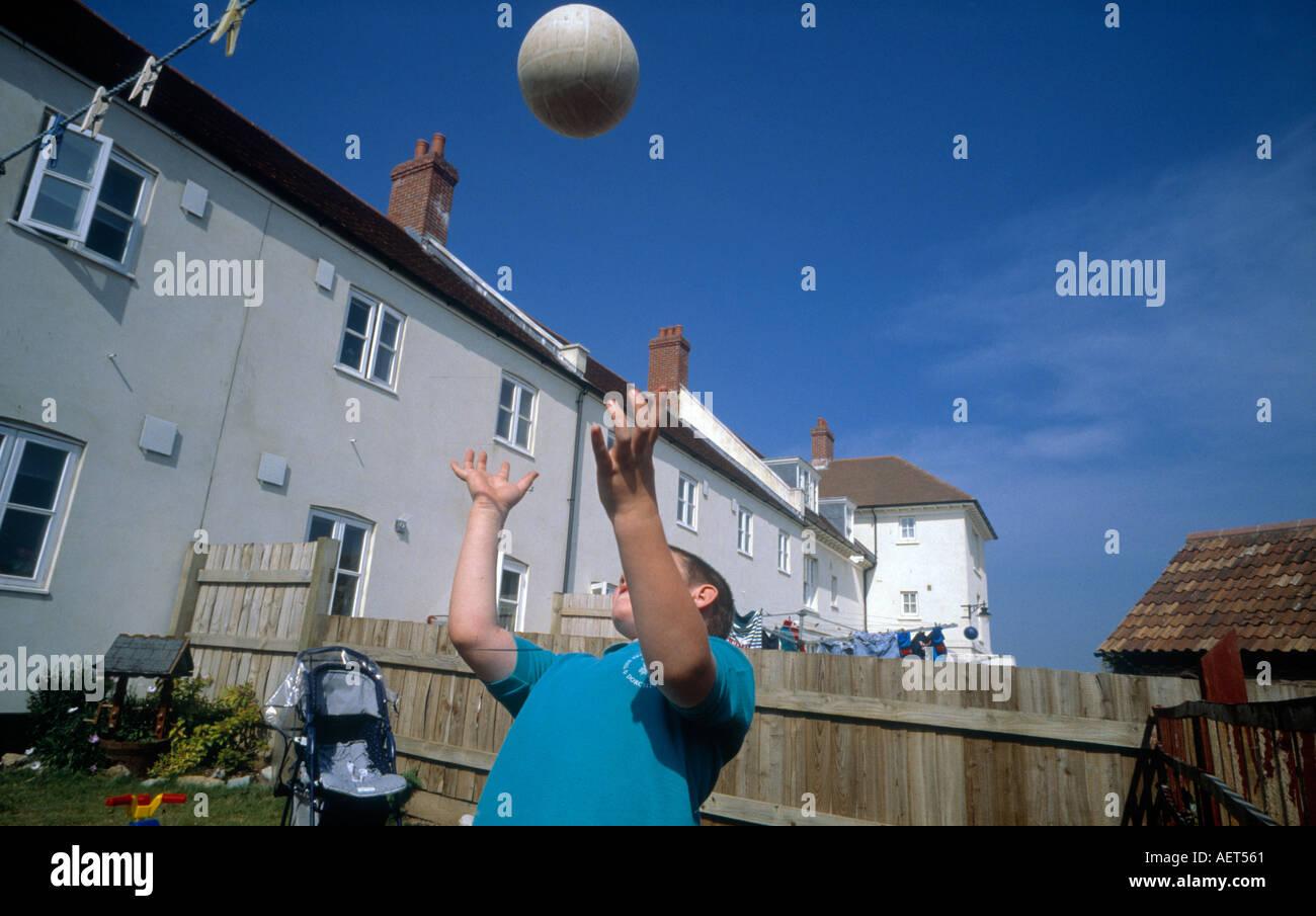 school boy with prince of wales school logo sweatshirt playing football  in Poundbury Dorset - Stock Image