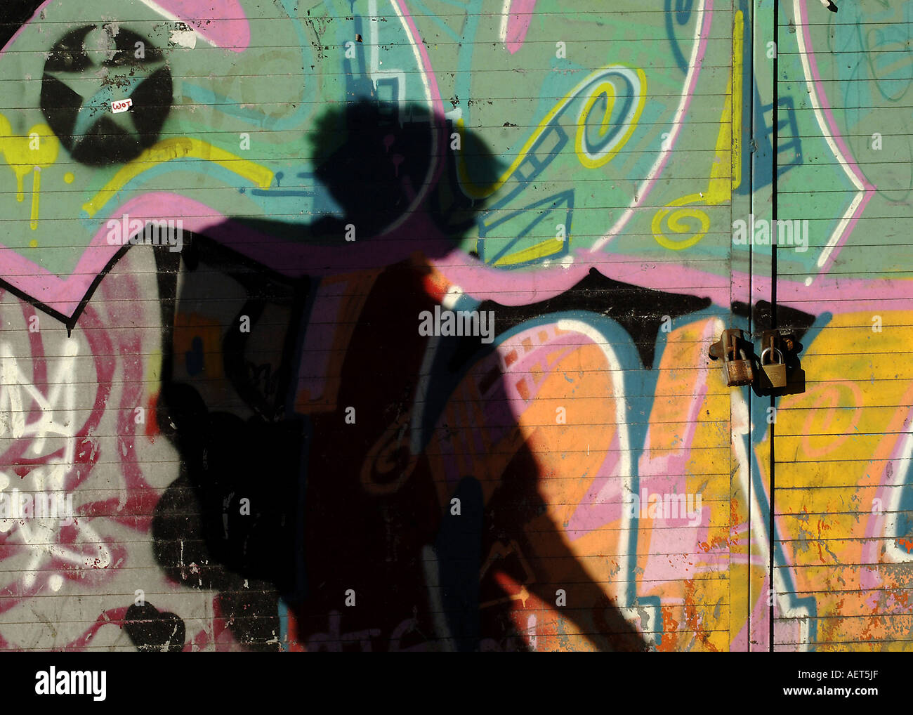 Pedestrians shadows refected against a graffitti background, Old Street, East london, UK - Stock Image