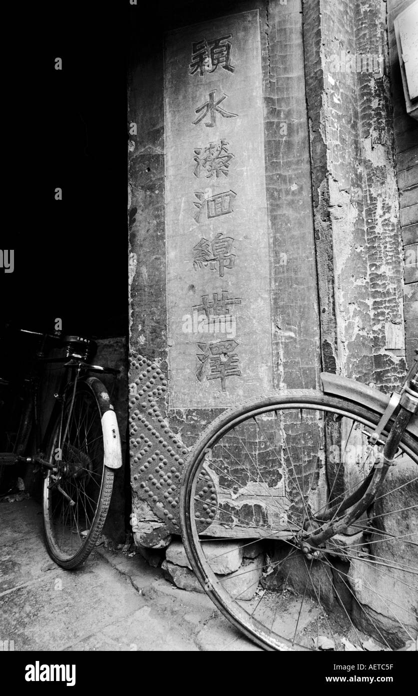 Bicycles parked beside an old door in a Beijing hutong 2003 China - Stock Image