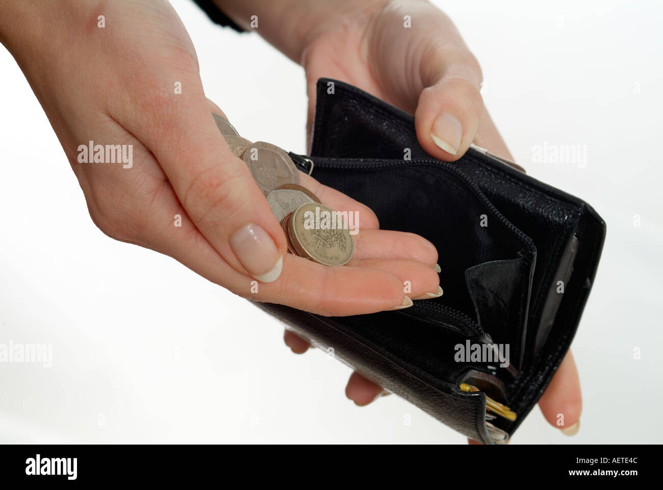 hand with loose change and a black purse - Stock Image