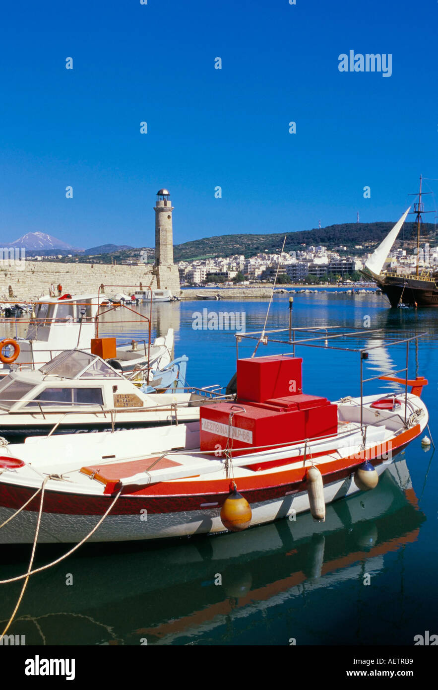 View of old Venetian Rethymo harbour and lighthouse in background Rethymno Rethymnon island of Crete Greece Mediterranean Stock Photo