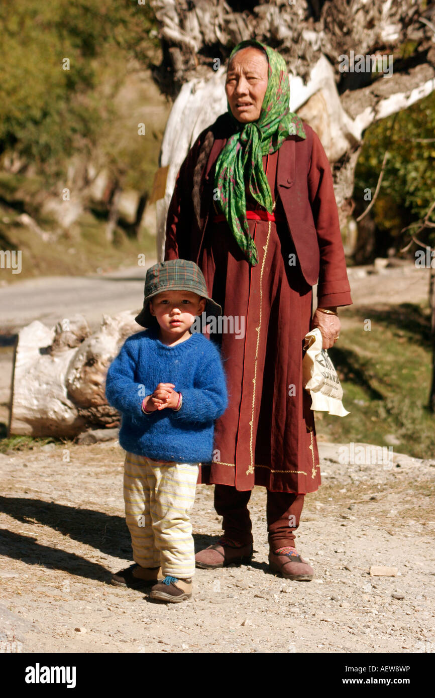 Buddhist lady waiting for the bus to arrive to go to the village to buy grocery at  Keylong, Himachal Pradesh India - Stock Image