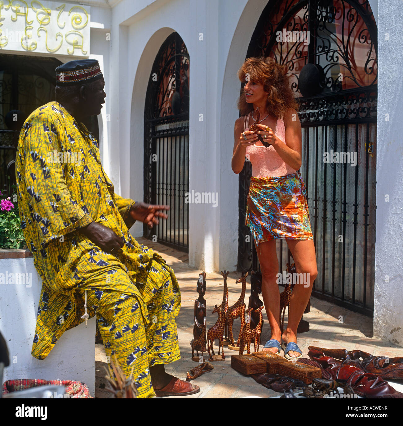Woman Buying Goods From African Trader In Marbella Costa Del Sol Spain Europe - Stock Image