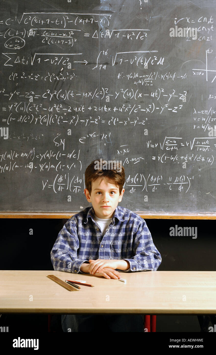 Young boy caucasian sitting in front of a blackboard filled with einstein calculations - Stock Image