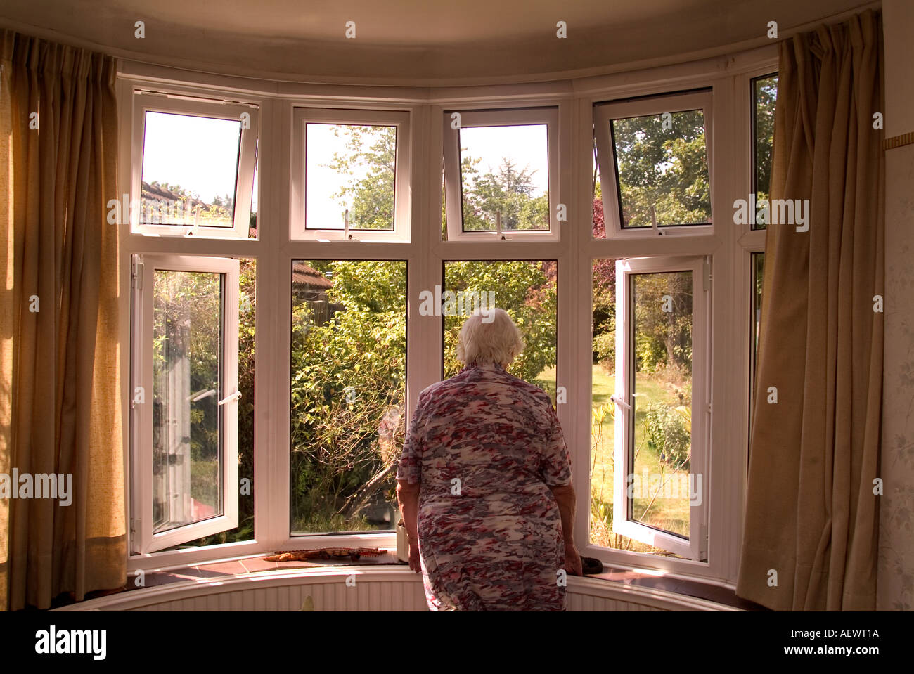 81 year old elderly woman looking out of her front room window, London, UK. Model Released image (MR). Stock Photo
