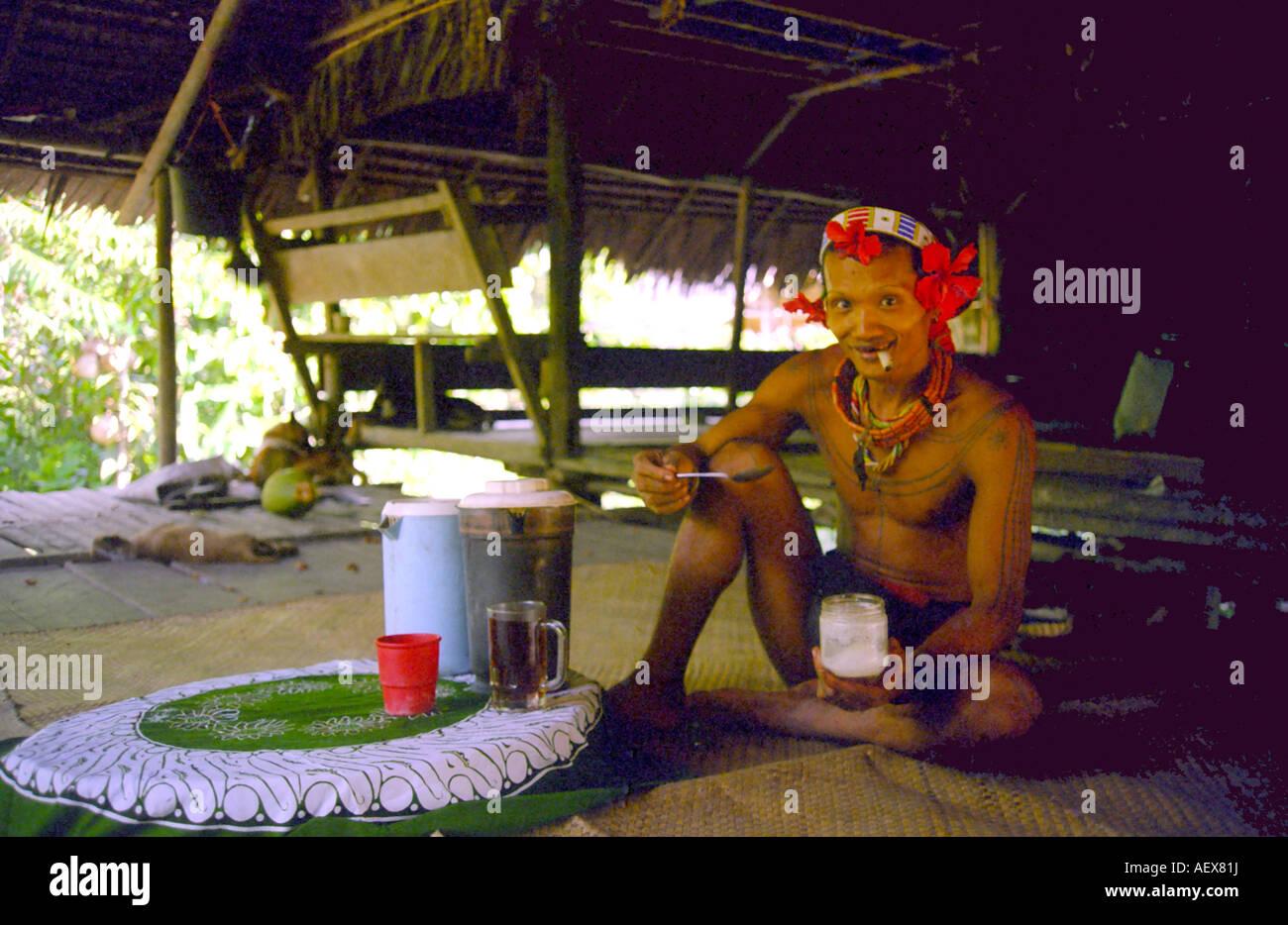 Mentawai man having tea on Siberut Island off Sumatra in Indonesia - Stock Image