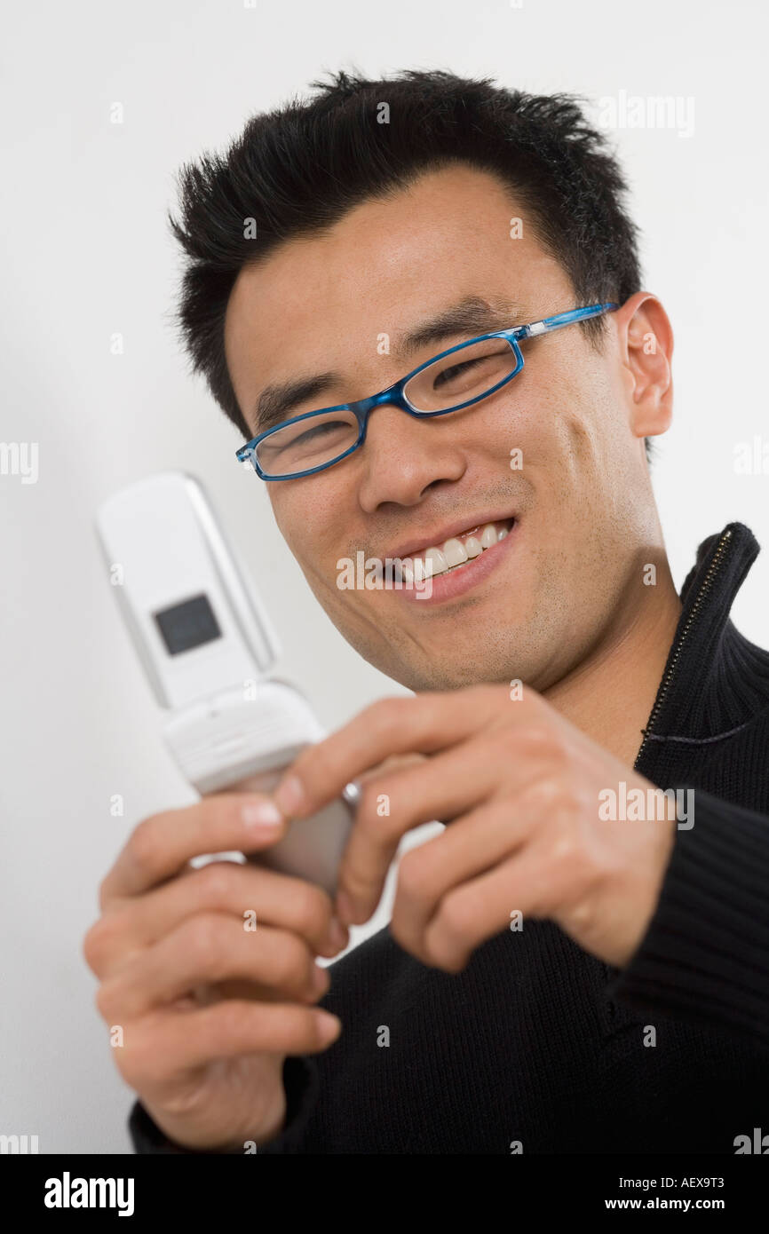 Young man using a mobile phone - Stock Image