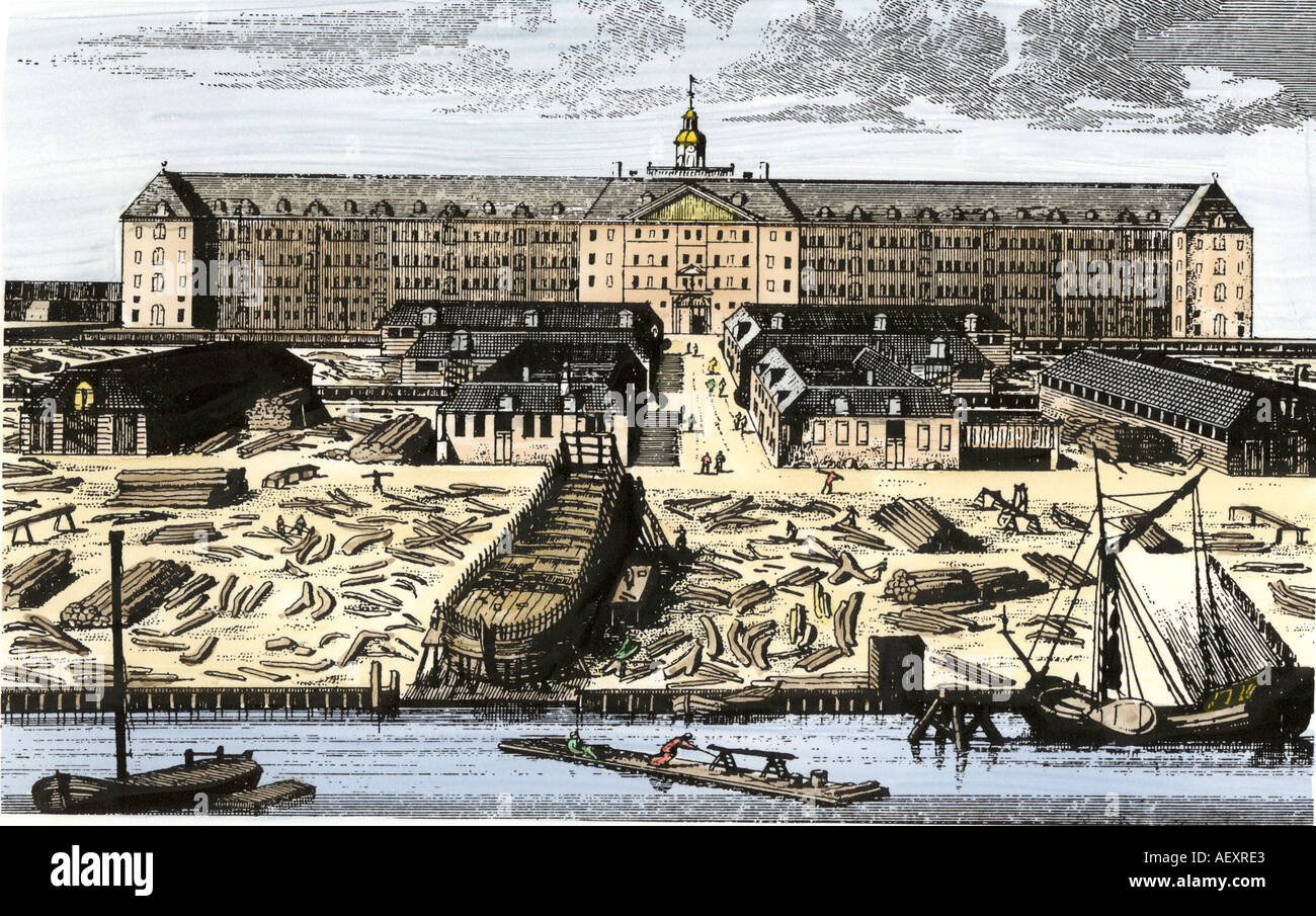 Dutch East India Company in Amsterdam showing warehouses and shipyard. Hand-colored woodcut - Stock Image