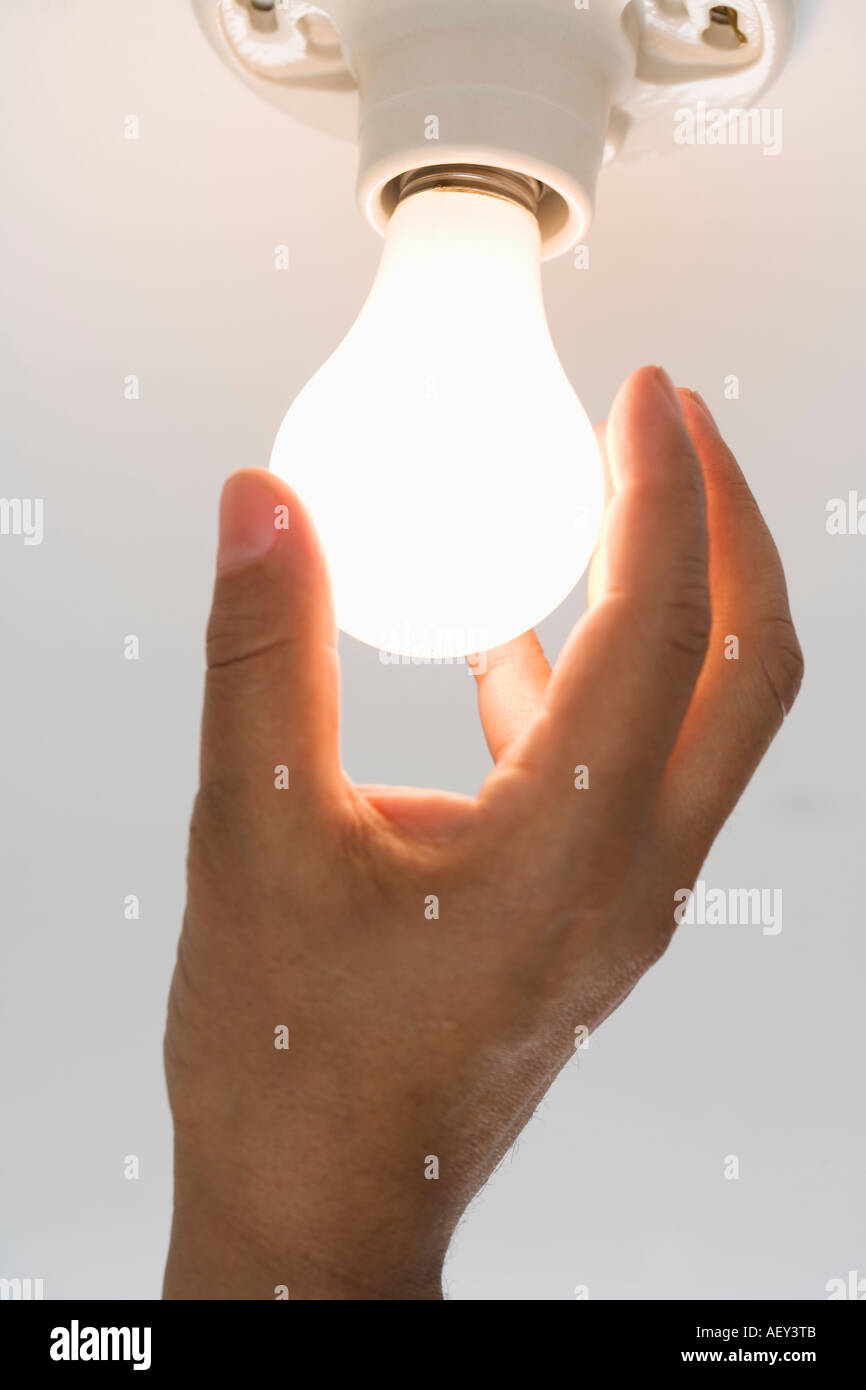 Close up of lightbulb being screwed in - Stock Image