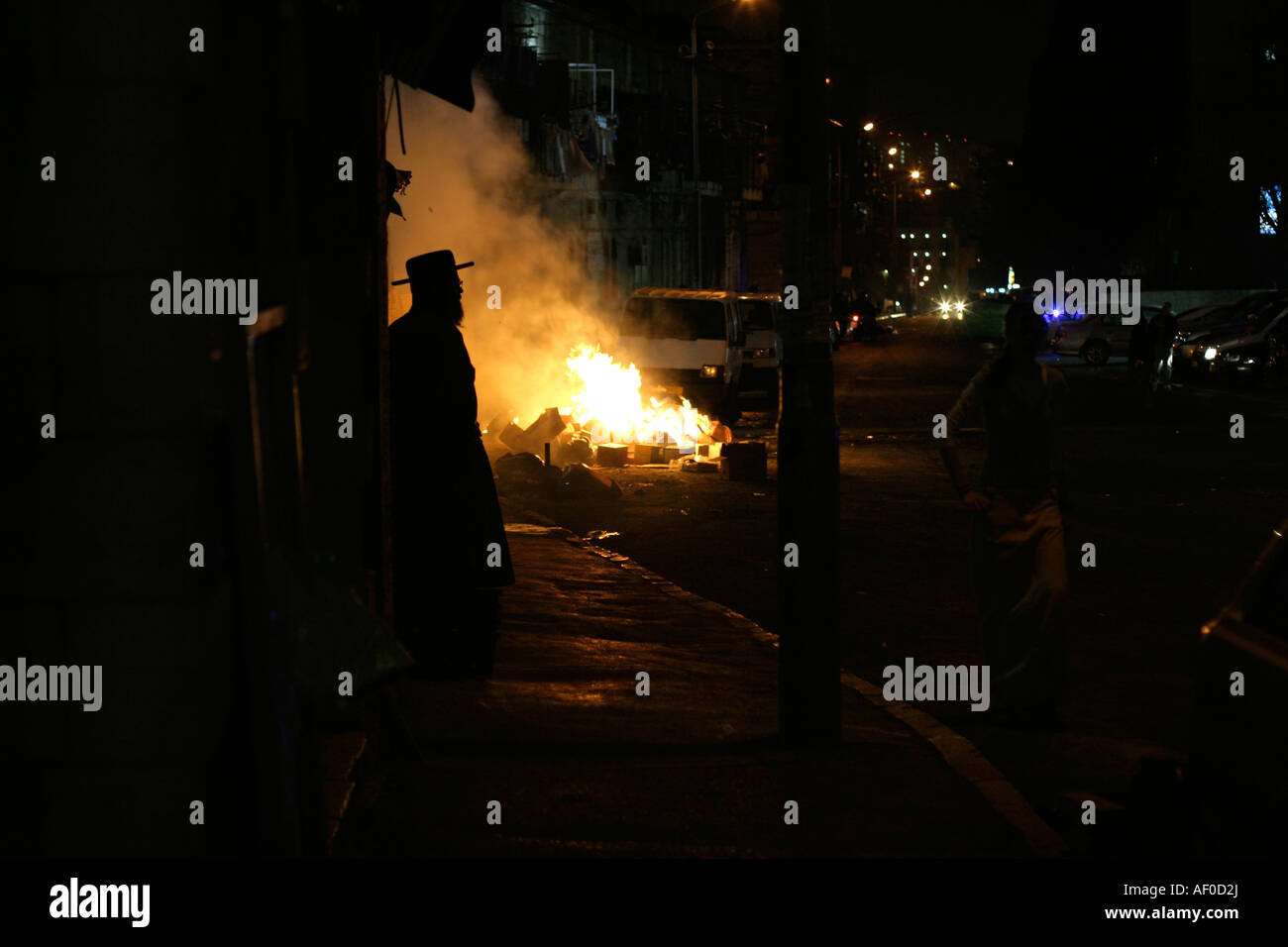 silhouette of hasidic jew standing in front of blazing riot fires jerusalem israel Stock Photo