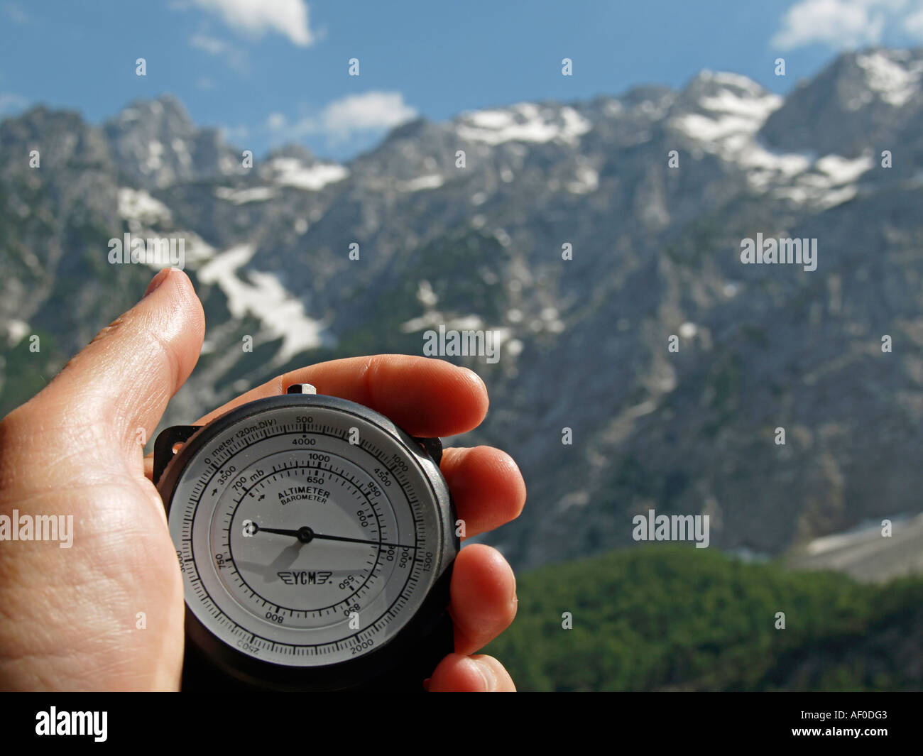 MR hand holding altimeter showing a height of 1500 meters in front of mountains with snow covered tops - Stock Image