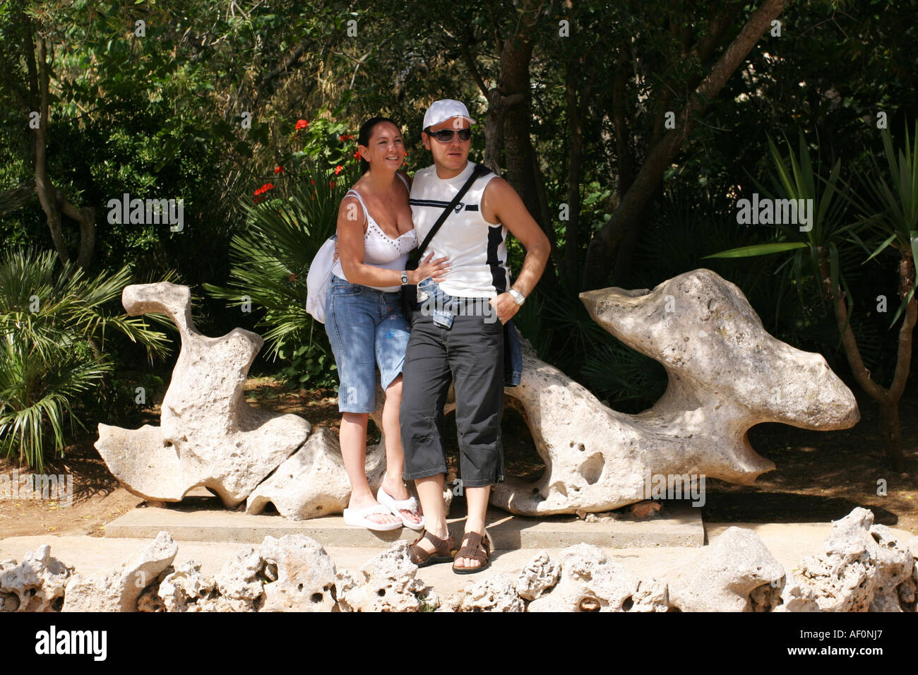 Tourists By The Dragon Stone That Is Symbol Of Cuevas Del Drach Or Coves Drac Caves Mallorca Spain