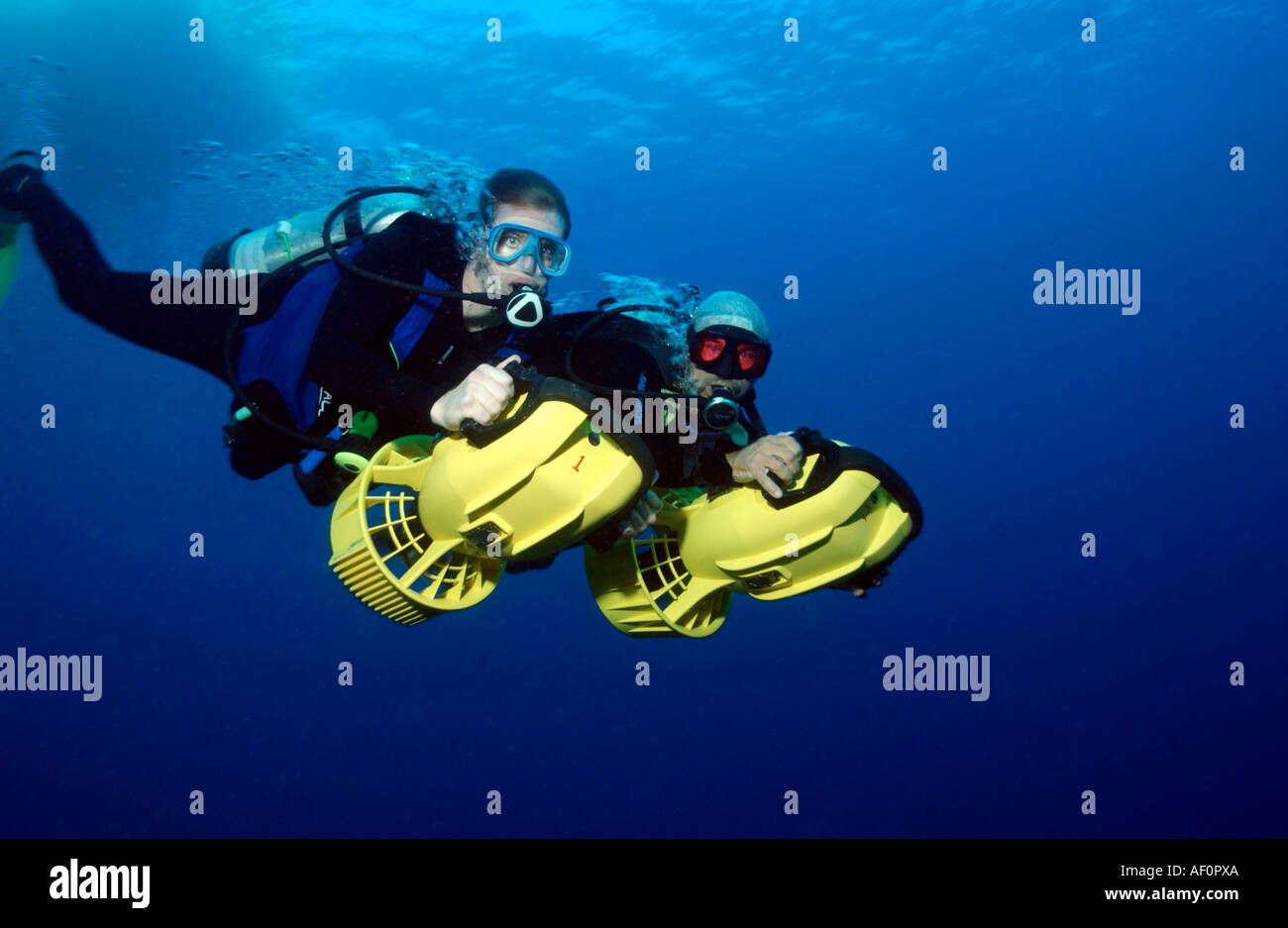 Scuba divers underwater on Dive Propulsion Vehicles DPV or scooters - Stock Image