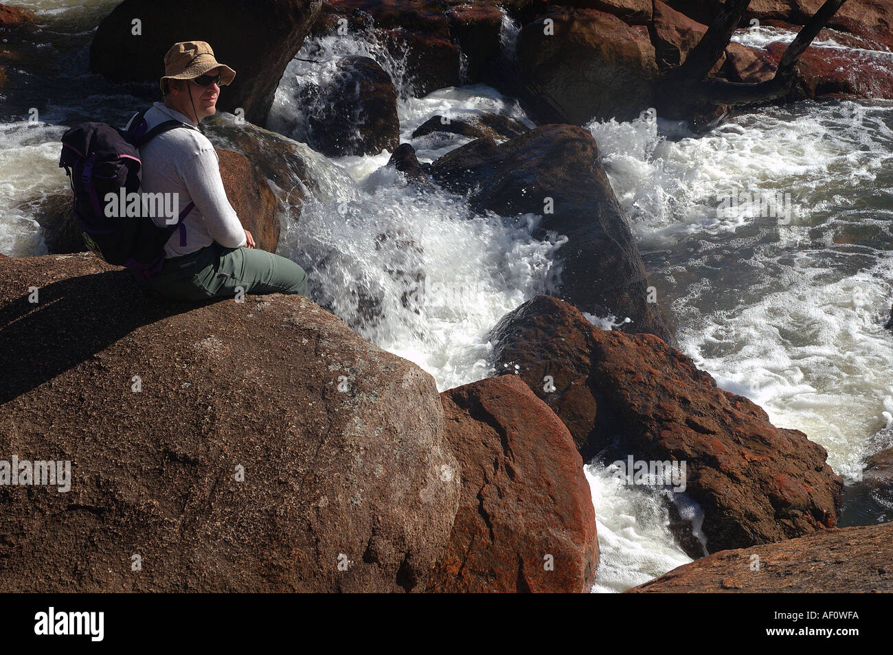 Bushwalker resting on a boulder in Jane Brook John Forrest National Park, Darling Ranges, Perth, Western Australia - Stock Image