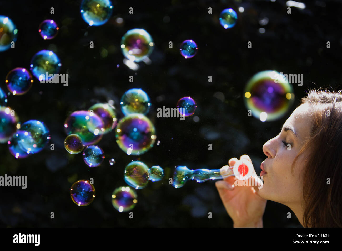 Woman with soap bubbles, Junge Frau blaest Seifenblasen in die Luft Stock Photo