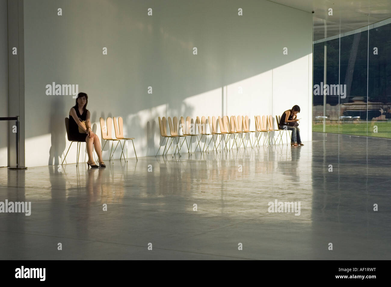 Two women waiting in the foyer of the 21st Century Museum of Contemporary Art, Kanazawa, Japan - Stock Image
