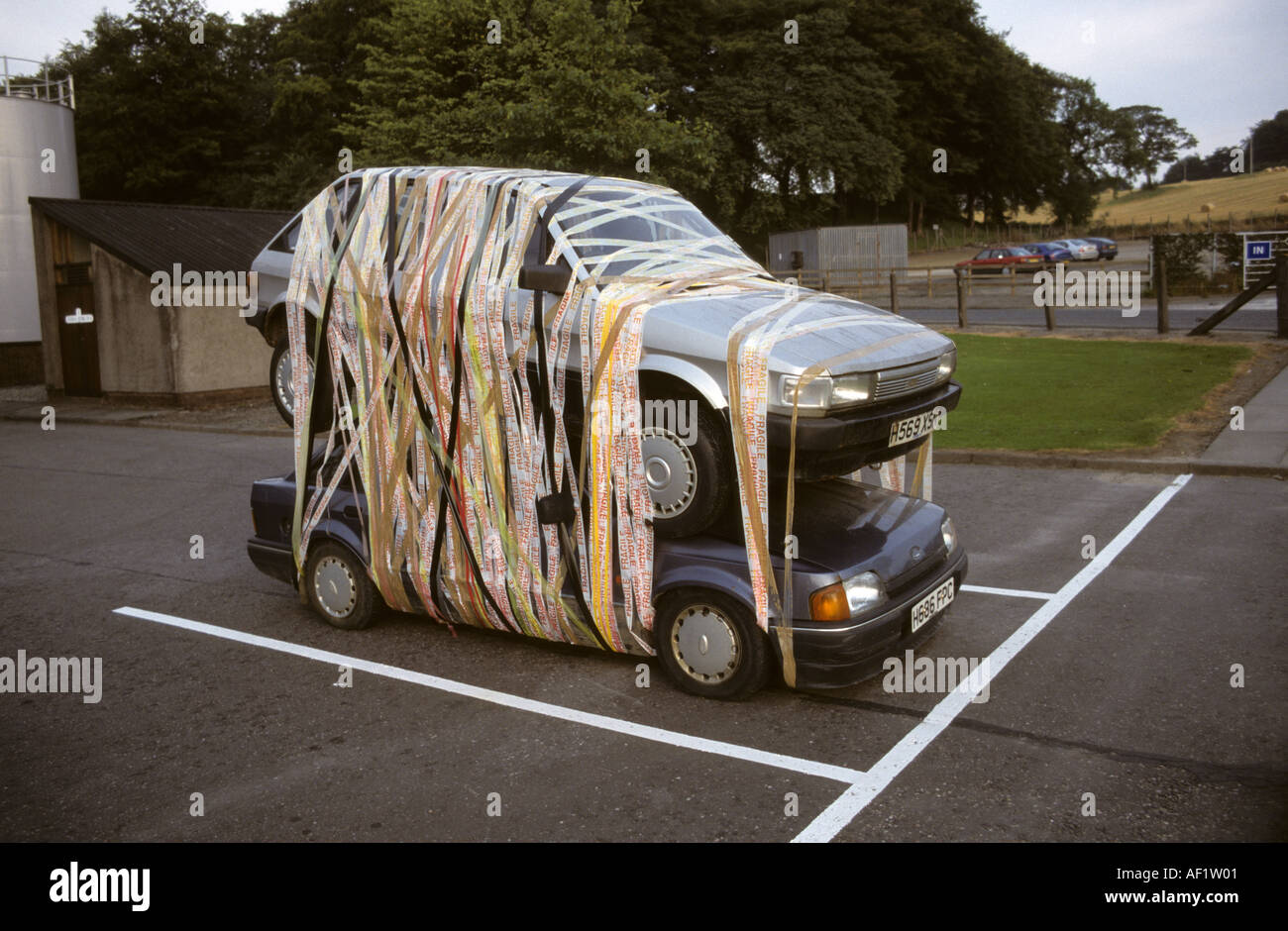 Car Art Practical Joke taping two cars together on top of each other - Stock Image