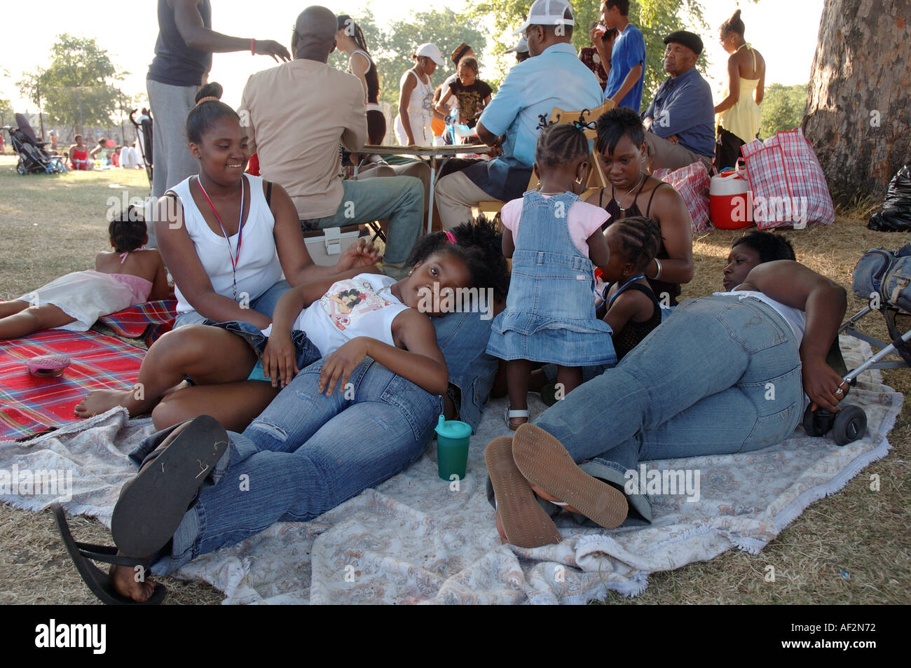 Extended family picnicking and relaxing in Brockwell park in summer. - Stock Image