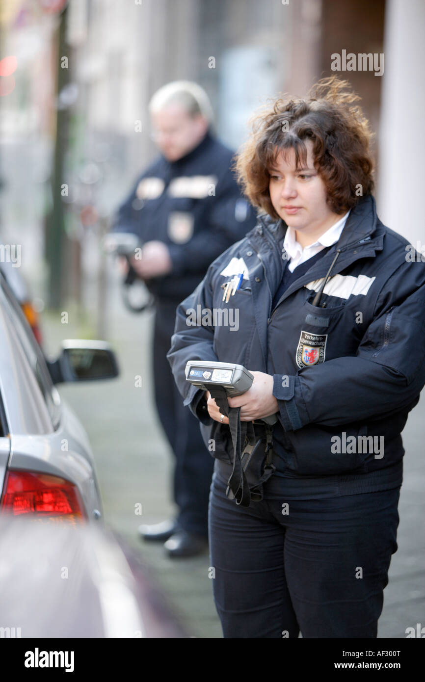 Traffic wardens distributes parking ticket to parking offenders - Stock Image