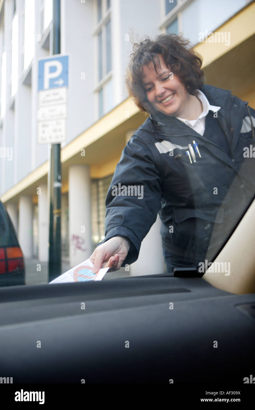 Traffic warden distributes parking ticket to parking offenders - Stock Image