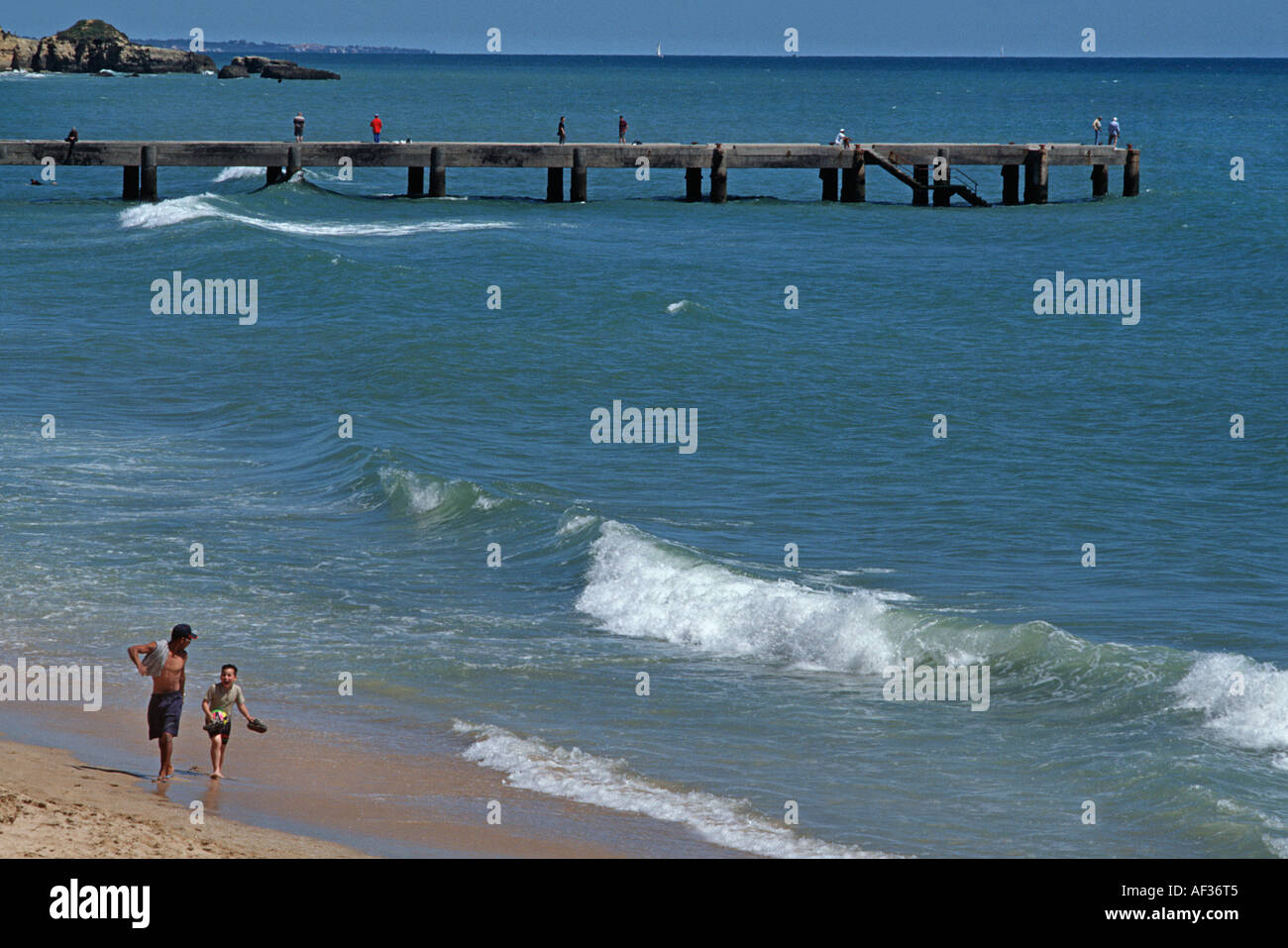walking along the shoreline at Albufeira Algarve Portugal Jetty with fishermen in background - Stock Image
