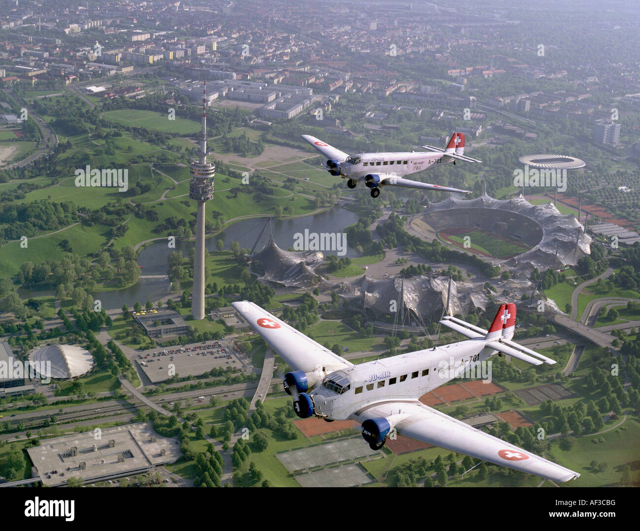 two Junkers Ju 52 aeroplanes flying over Olympia Stadion Munich, Germany, Bavaria, Muenchen - Stock Image