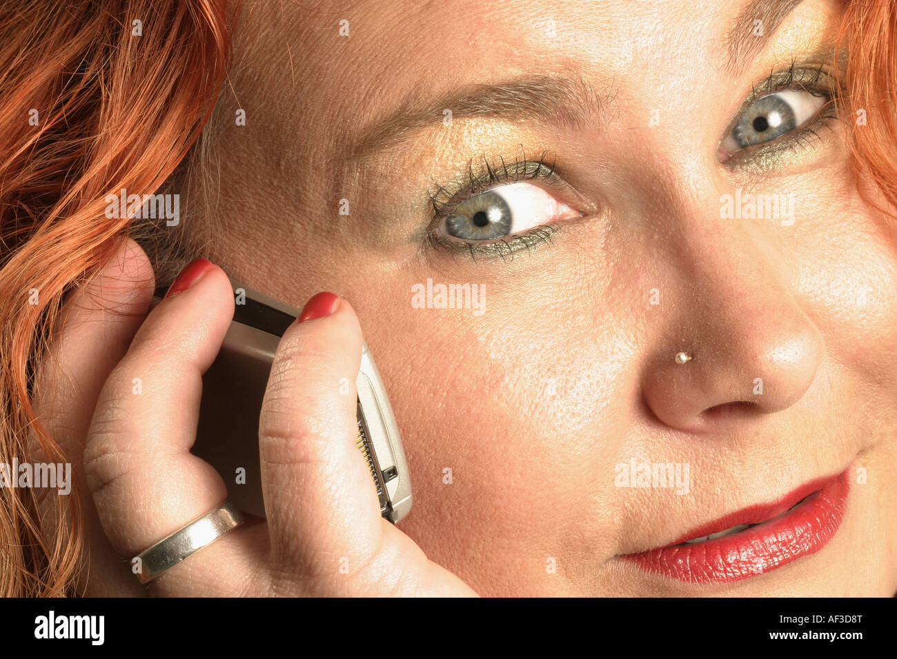 redheaded woman calling with mobile telephone, Germany - Stock Image
