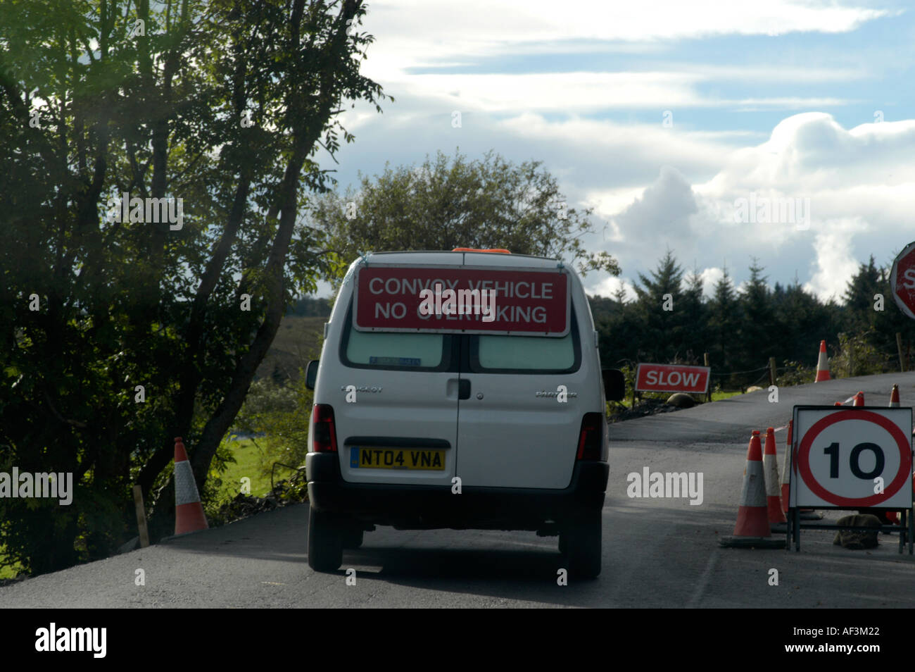 white van with no overtaking sign on single lane road Stock