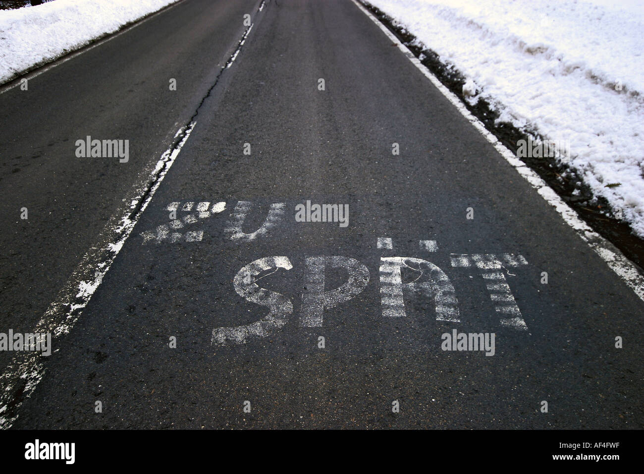 Characters 'zu spaet' means 'too late' written on the asphalt of a road - Stock Image