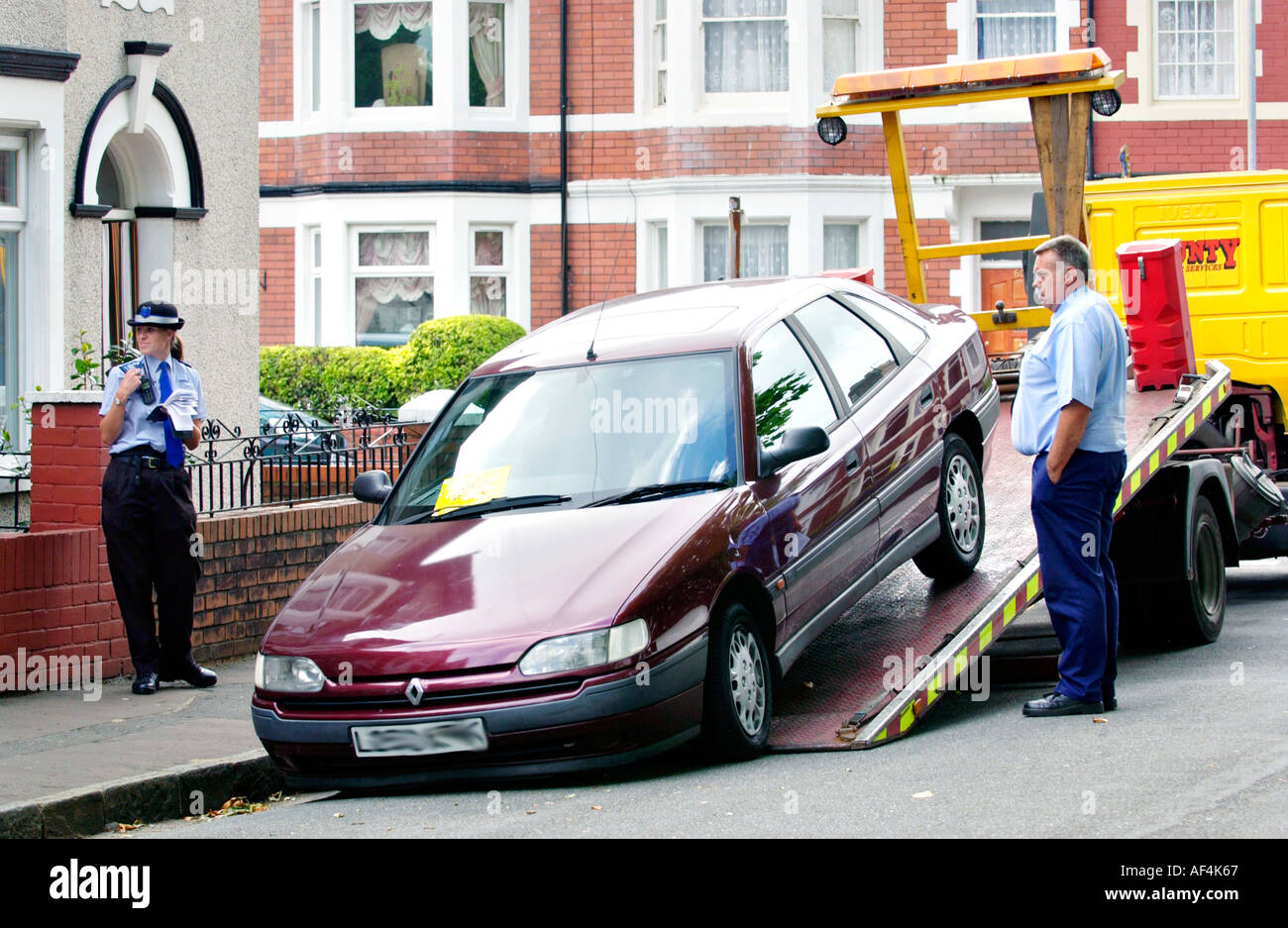 Untaxed car being taken away on a low loader in a DVLA operation on street in Newport South Wales UK Stock Photo