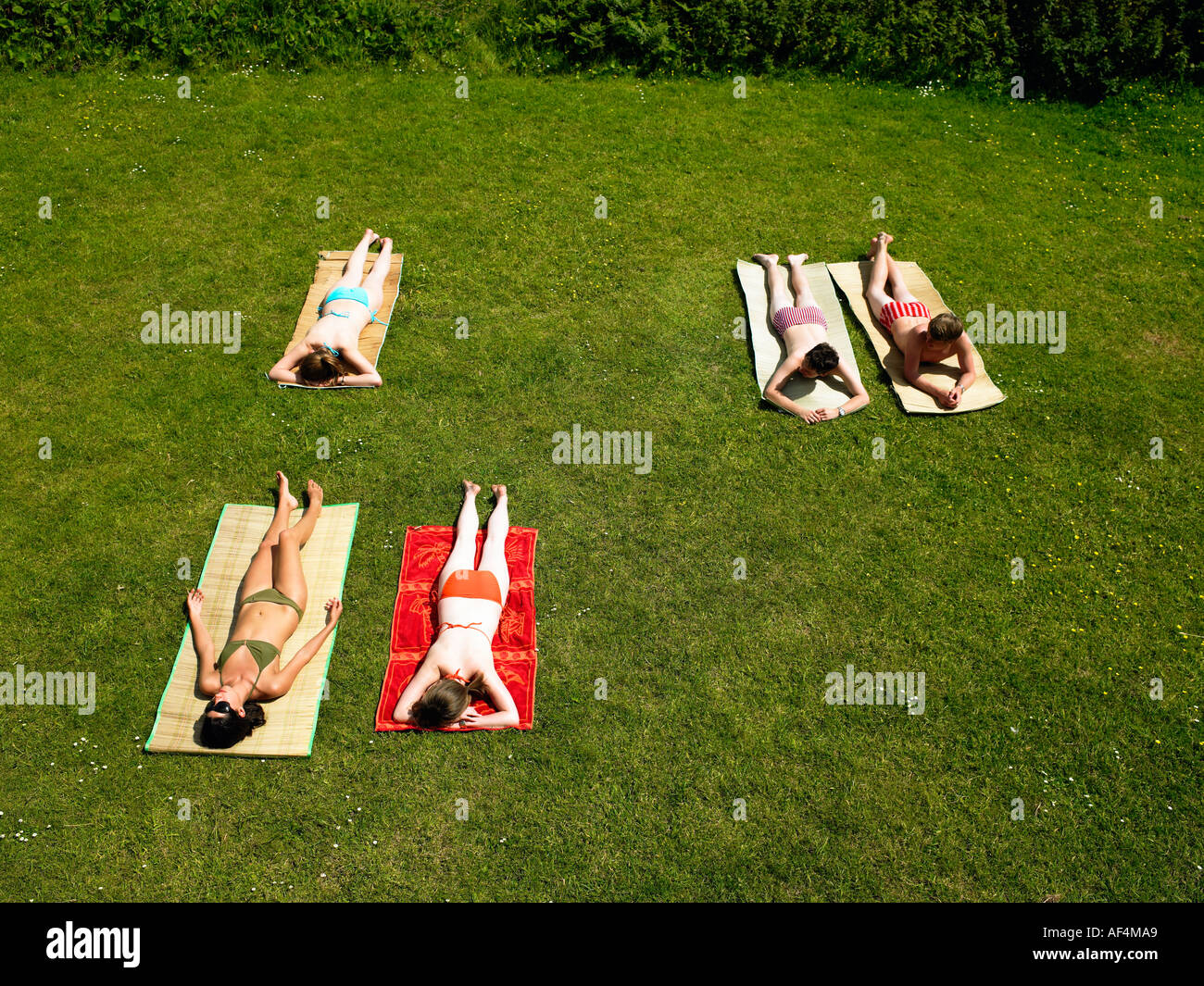 Young people sunbathing in a garden - Stock Image