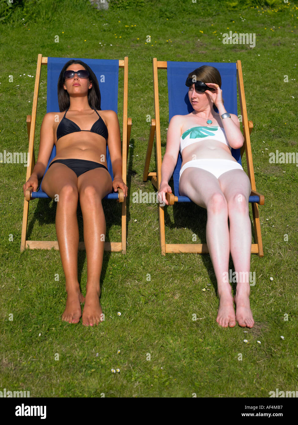 Two Girls Sunbathing on Deck Chairs One is tanned one is pale - Stock Image