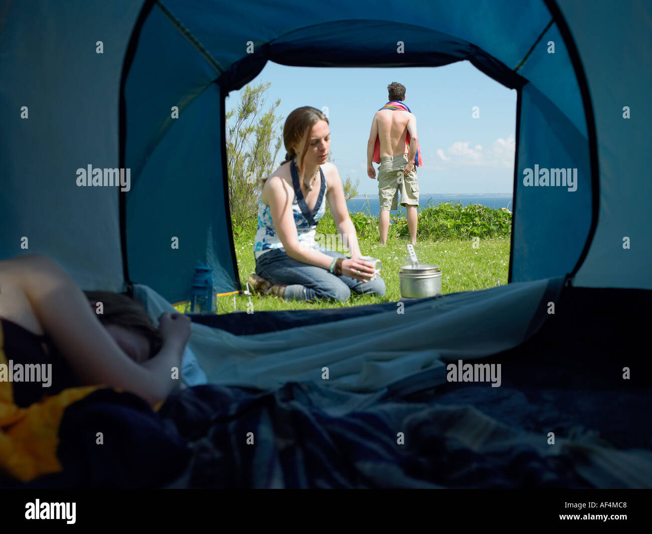 View through tent opening with young female sleeping inside whilst another cooks outside with a young male standing - Stock Image