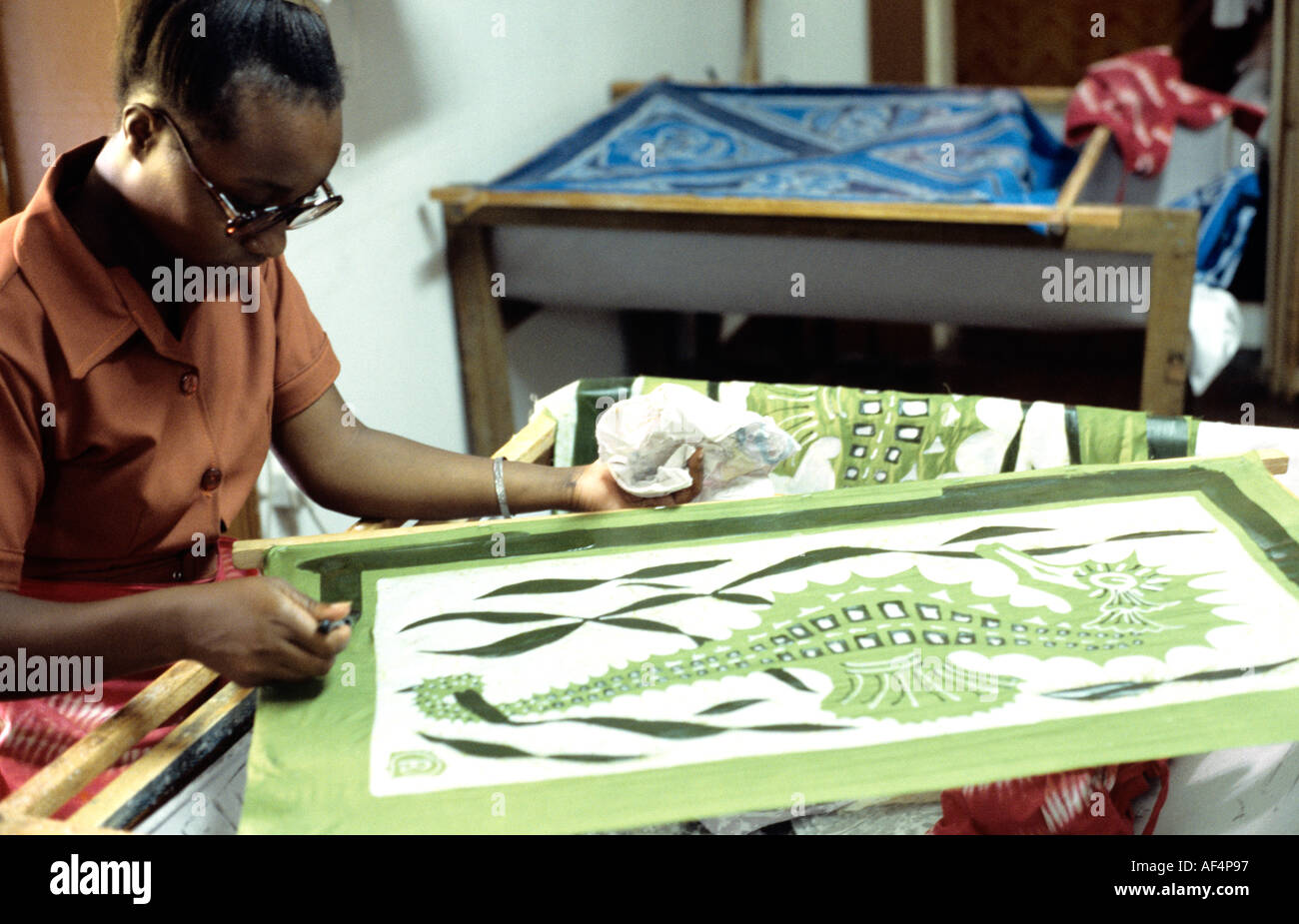 Local man works on batik of green seahorse in a workshop on St Kitts The Caribbean West Indies - Stock Image