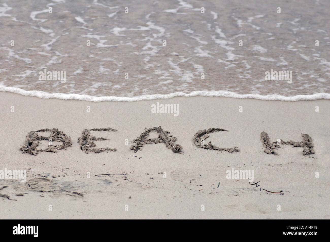 The word BEACH is written in the sand by the sea - Stock Image