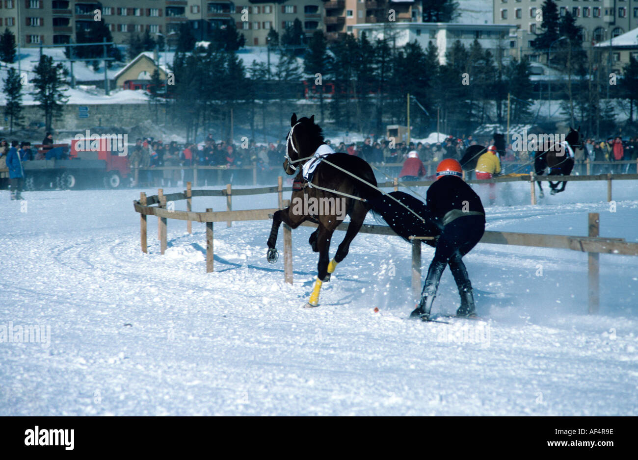 Horse and ski racing teams negotiate a curve on the race track on frozen lake at St Moritz The Engadin Switzerland - Stock Image