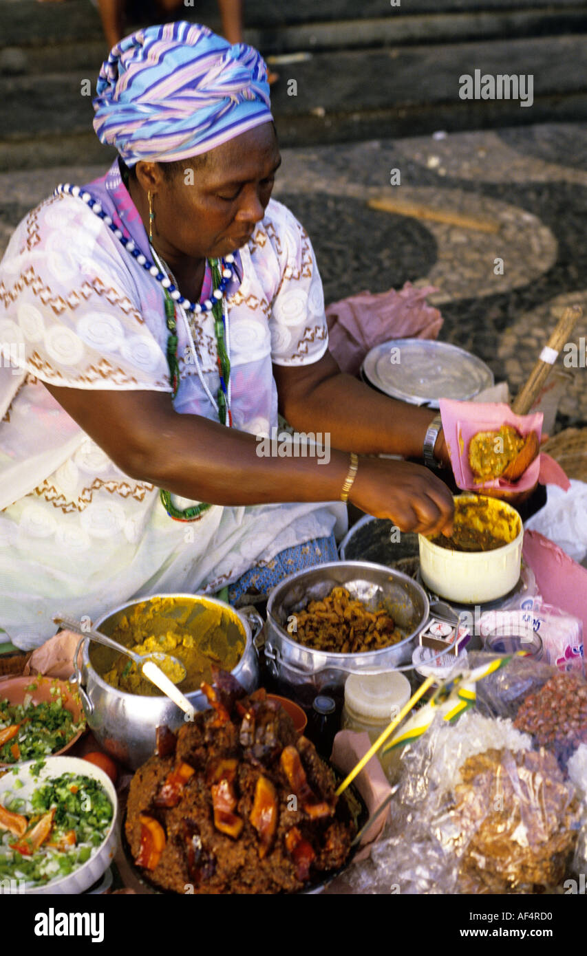 Typical lady street food vendor in traditional local white dress and stripped headdress Salvador Bahia State Brazil - Stock Image