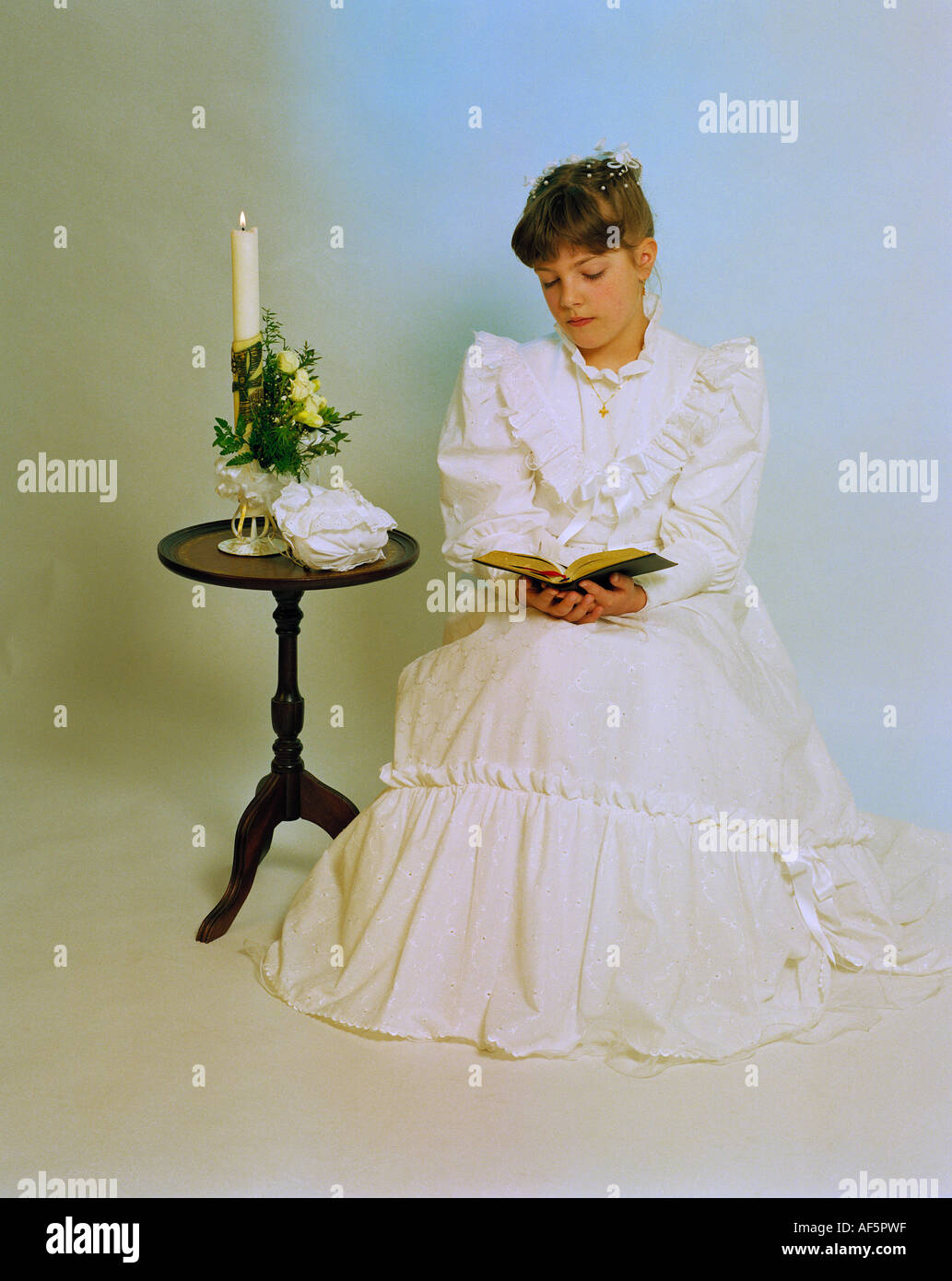 Roman Catholic Church, Holy Communion, girl holding a prayer book and a burning candle - Stock Image