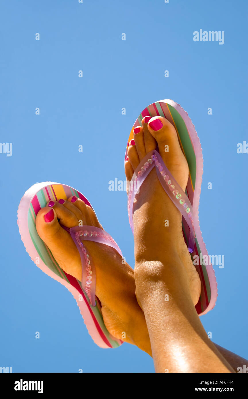 71940e9ce Vertical close up of a woman s tanned feet with painted toenails wearing  striped flip flops against