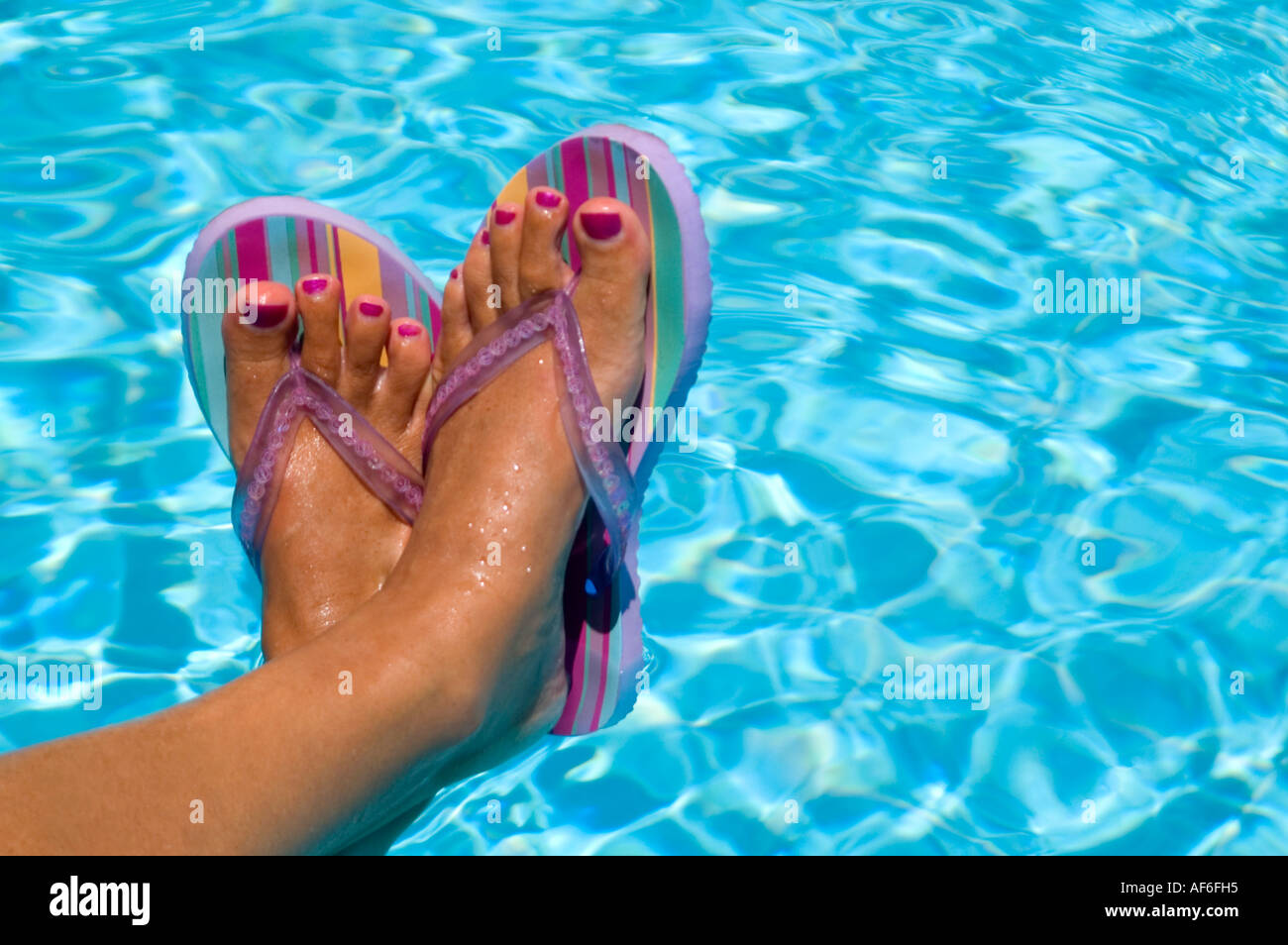 b03443b9a Horizontal close up of a woman s tanned feet with painted toenails wearing  striped flip flops against