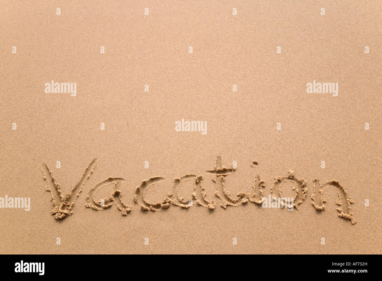 Vacation handwritten in sand plenty of copy space - Stock Image