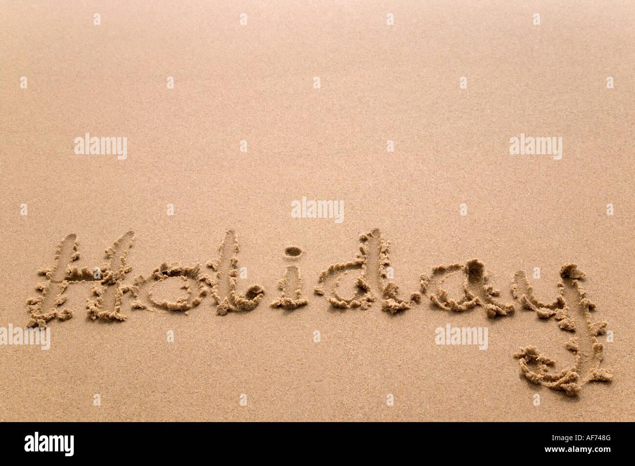Holiday handwritten in golden sand plenty of copy space - Stock Image