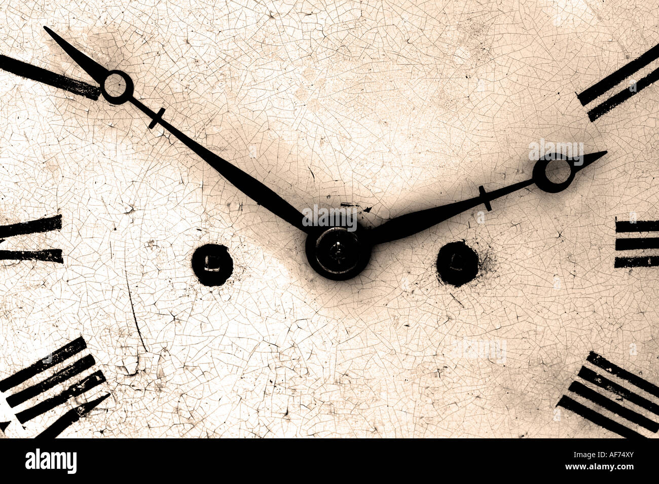 Close up of an antique clock face dark and grainy sepia toned - Stock Image