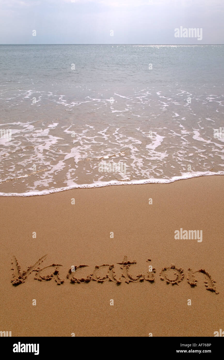 Vacation written in sand on the beach - Stock Image