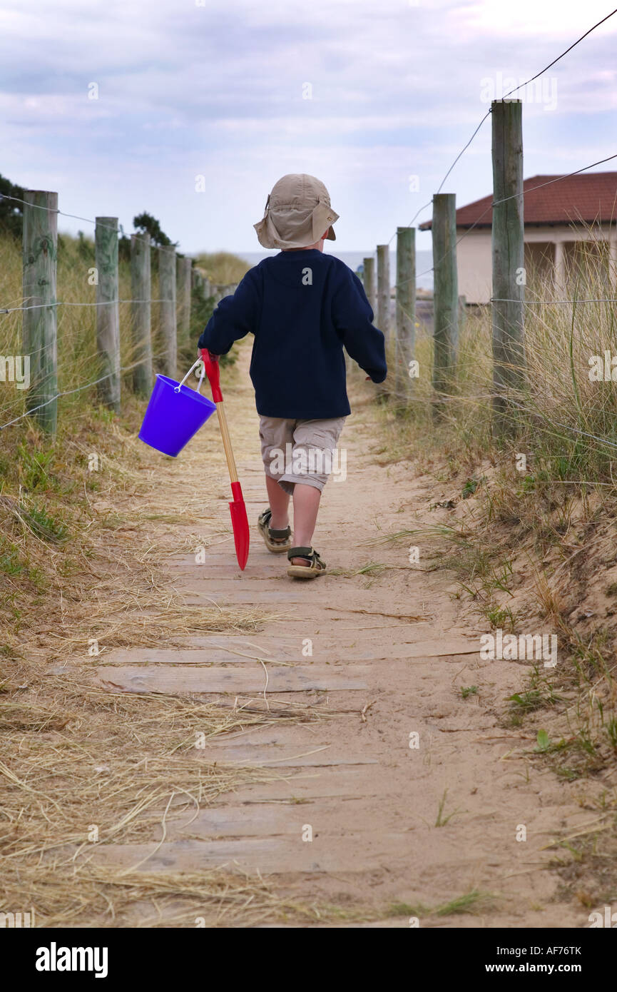 Toddler off to the beach despite the gloomy weather - Stock Image